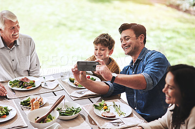 Buy stock photo High angle shot of an affectionate father taking a selfie with his son during lunch outdoors