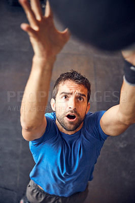 Buy stock photo High angle shot of a handsome young man working out with a medicine ball in the gym