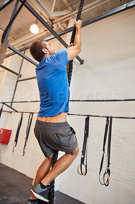 Buy stock photo Full length shot of a handsome young man rope climbing while working out in the gym
