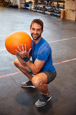 Buy stock photo High angle portrait of a handsome young man working out with a medicine ball in the gym