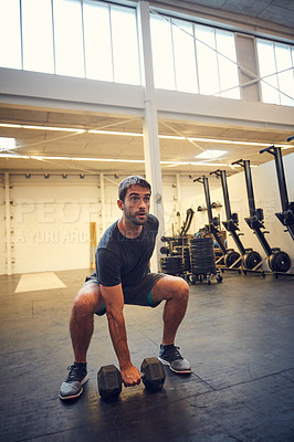 Buy stock photo Full length shot of a handsome young man working out with a dumbbell in the gym