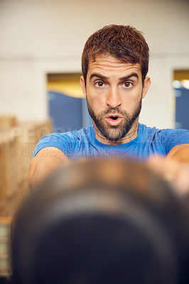 Buy stock photo Cropped portrait of a handsome young man working out with a kettle bell in the gym