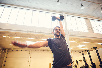 Buy stock photo Low angle shot of a handsome young man working out with a dumbbell in the gym