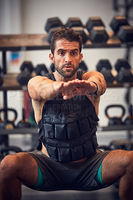 Buy stock photo Cropped shot of a handsome young man doing squats while working out in the gym