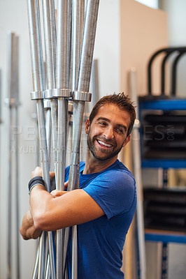 Buy stock photo Cropped shot of a handsome young man carrying equipment while working out in the gym