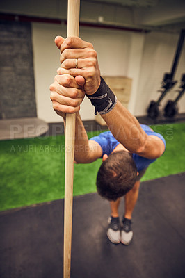 Buy stock photo Full length shot of a handsome young man working out with a stick in the gym
