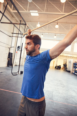Buy stock photo Cropped shot of a handsome young man working out with a stick in the gym