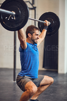 Buy stock photo Cropped shot of a handsome young man lifting weights while working out in the gym