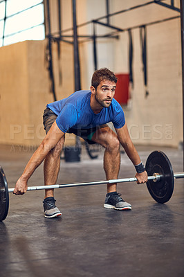 Buy stock photo Full length shot of a handsome young man lifting weights while working out in the gym