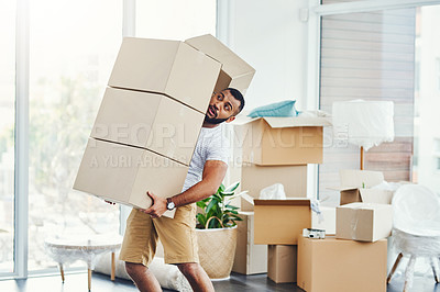Buy stock photo Shot of a young man carrying a pile of boxes while moving house