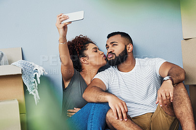Buy stock photo Shot of a young couple taking selfies while moving house