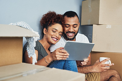 Buy stock photo Shot of a young couple using a digital tablet while moving house
