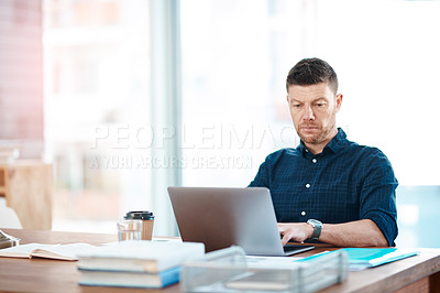 Buy stock photo Shot of a businessman using a laptop at his desk in a modern office