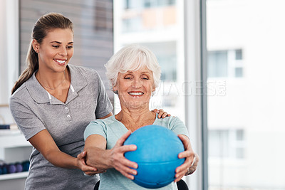 Buy stock photo Shot of a senior woman using a ball during a consultation with a physiotherapist