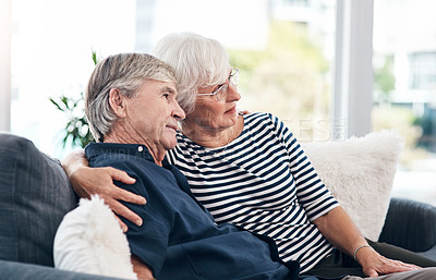 Buy stock photo Shot of a happy senior couple looking thoughtful while relaxing together on the sofa at home