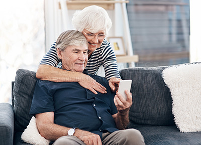 Buy stock photo Shot of a happy senior couple using a smartphone while relaxing together on the sofa at home