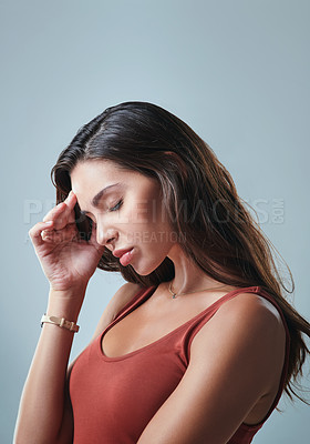 Buy stock photo Studio shot of a beautiful young  woman looking stressed against a grey background