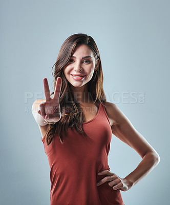 Buy stock photo Studio shot of a young woman showing the peace sign against a grey background