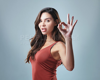 Buy stock photo Studio shot of a young woman showing the ok sign against a grey background