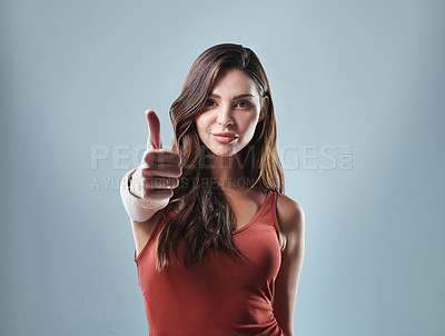 Buy stock photo Studio shot of a young woman showing thumbs up against a grey background