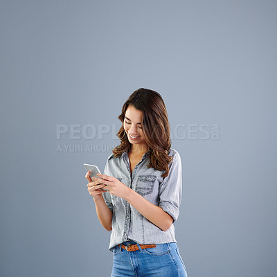 Buy stock photo Studio shot of an attractive young woman sending a text message against a grey background