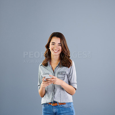 Buy stock photo Studio portrait of an attractive young woman sending a text message against a grey background