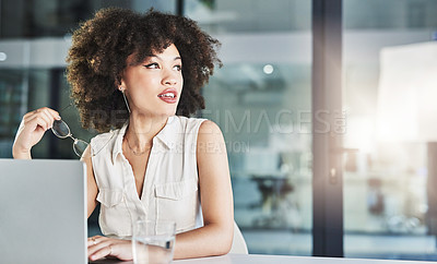 Buy stock photo Cropped shot of a cheerful young businesswoman seated at her desk while looking into the distance inside of the office during the day