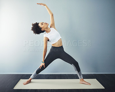 Buy stock photo Shot of a young woman practicing yoga inside of a yoga studio during the day