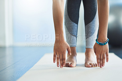 Buy stock photo Shot of an unrecognizable young woman practicing yoga inside of a yoga studio during the day
