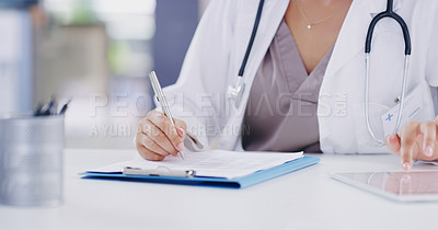 Buy stock photo Cropped shot of a doctor using a digital tablet while going through paperwork in a modern hospital