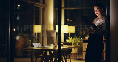 Buy stock photo Shot of a beautiful young businesswoman using a digital tablet while working late in her office
