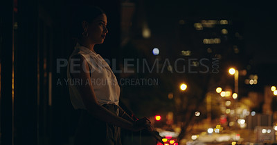 Buy stock photo Shot of a beautiful young businesswoman taking a view of the city while standing on  a balcony at night