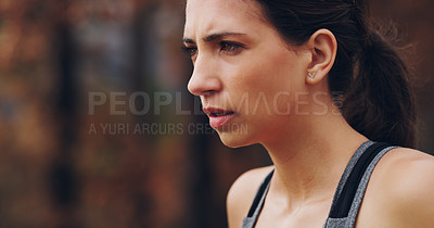 Buy stock photo Cropped shot of a sporty young woman looking determined while out exercising