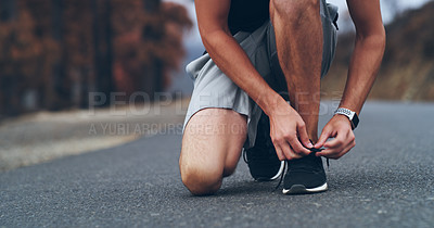 Buy stock photo Cropped shot of an unrecognizable man tying his shoelaces while out for a run