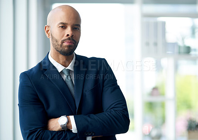 Buy stock photo Portrait of a handsome young businessman posing with his arms folded inside his office