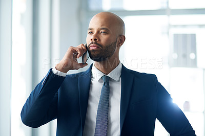 Buy stock photo Shot of a handsome young businessman taking a phone call inside his office