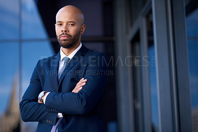 Buy stock photo Portrait of a handsome young businessman posing with his arms folded while standing outside an office building