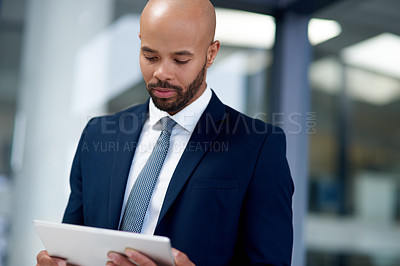 Buy stock photo Shot of a handsome young businessman using a digital tablet while his office