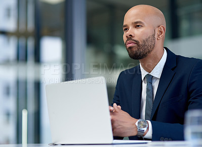 Buy stock photo Shot of a handsome young businessman looking thoughtful while working on laptop in his office