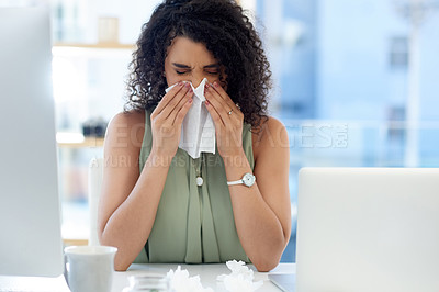 Buy stock photo Cropped shot of a young businesswoman blowing her nose while working at her desk in the office
