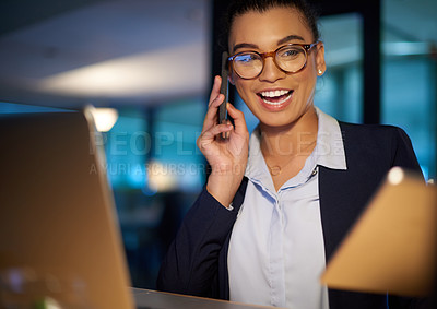 Buy stock photo Shot of a young businesswoman talking on a cellphone in an office at night