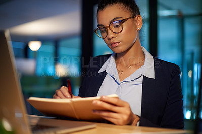Buy stock photo Shot of a young businesswoman writing notes while working in an office at night