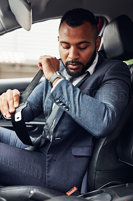 Buy stock photo Cropped shot of a well-dressed man fastening his seatbelt while driving a car