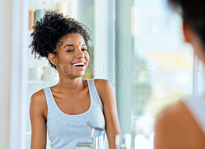 Buy stock photo Shot of an attractive young woman admiring herself in the bathroom mirror during her morning beauty routine