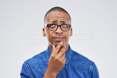 Buy stock photo Studio shot of a young man looking thoughtful against a gray background