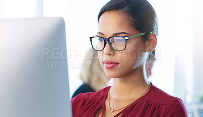 Buy stock photo Cropped shot of a focused young businesswoman working on her computer inside of the office