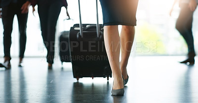Buy stock photo Low angle shot of an unrecognizable woman walking with her luggage inside a busy airport