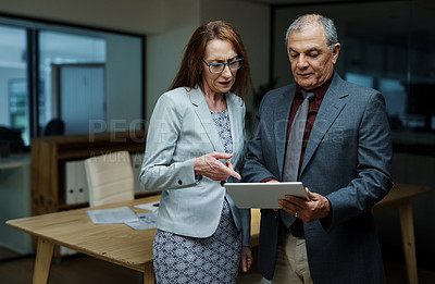 Buy stock photo Shot of two businesspeople using a digital tablet together in an office at night