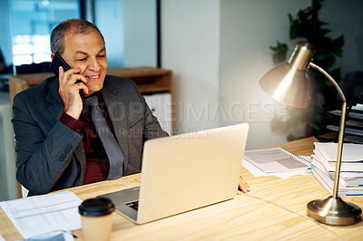 Buy stock photo Shot of a mature businessman talking on a cellphone while working on a laptop in an office at night