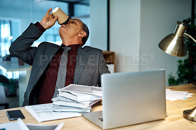Buy stock photo Shot of a mature businessman drinking coffee while working in an office at night
